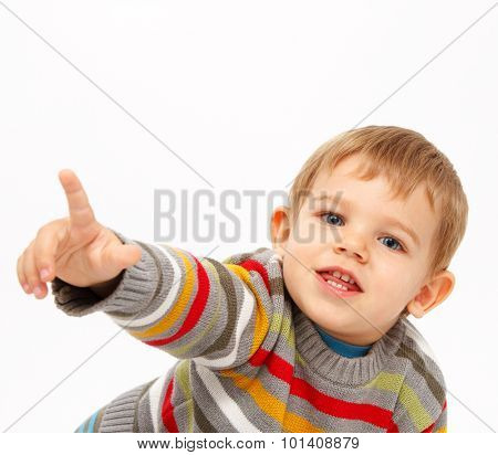 Boy in winter clothes pointing towards something