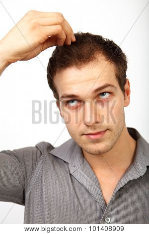 Hair loss concept - young man worried about baldness isolated on white