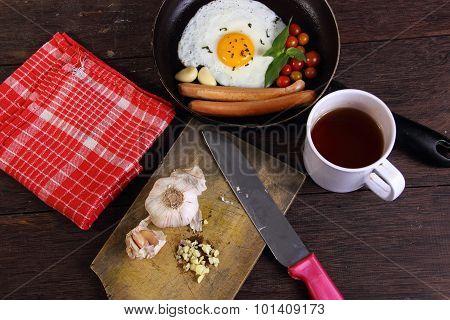 Bullseye Egg In Pan And Garlic On Chopping Board