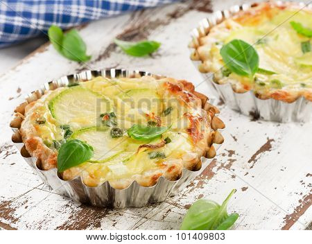 Tarts With Zucchini And Cheese On White Wooden Background.