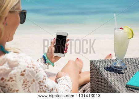 Woman using smartphone on the beach