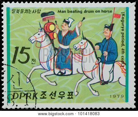 North Korea - Circa 1979: A Stamp Printed In North Korea, Shows Man Beating Drum On Horse From The S