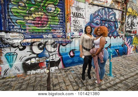 Women posing in front of colorful graffiti in Paris