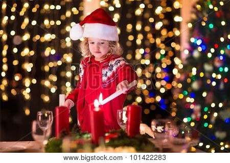Child Lighting A Candle At Christmas Dinner