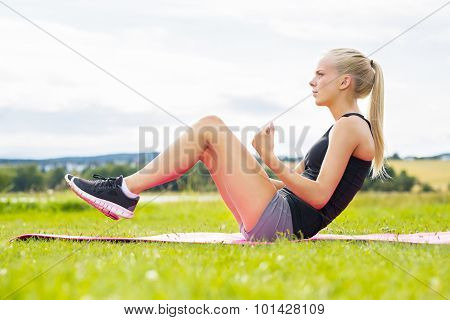 Young woman doing sit ups in the park