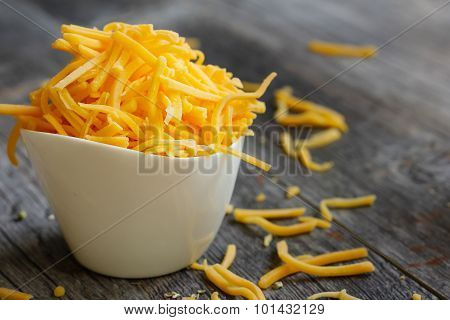Cheddar cheese in a white cup side view
