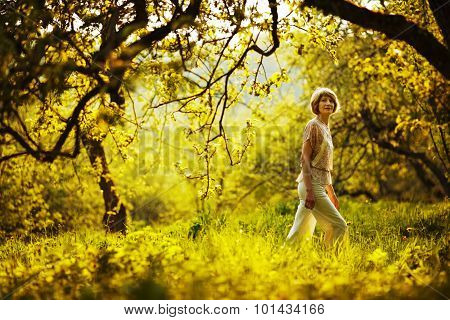 Woman Walking In Summer Apple Orchard
