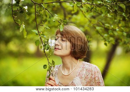 Happy Woman Inhales Aroma Of A Flower