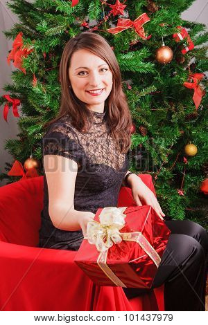Nice woman holding out red gift box