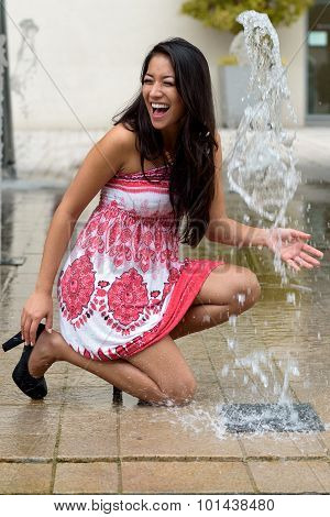Playful Trendy Young Woman Playing With A Fountain