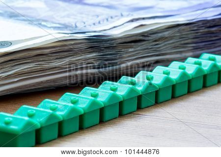 Green Plastic House Models In A Diagonal Row With Bank Notes