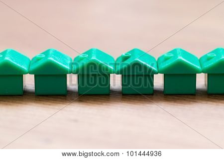 Green Plastic House Models In A Horizontal Row