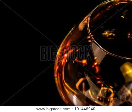 Top Of View Of Snifter Of Brandy In Elegant Typical Cognac Glass On Black Background With Red Reflec