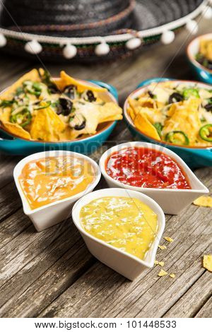 Nachos with melted cheese and salsa, guacamole and cheese dips