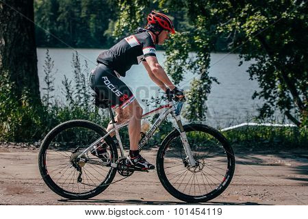 mountainbiker rides along lake