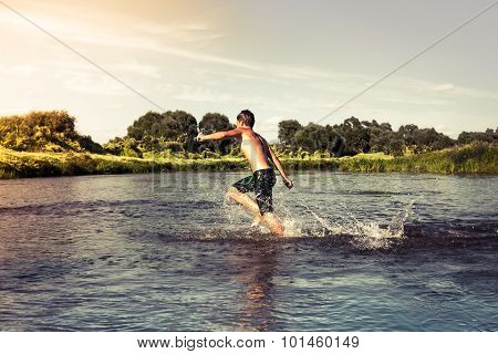 Young boy running forward on river shore during sunset