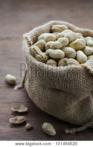 Peanuts in gunny bag on wood board back ground with dark mood photography, Still life with peanuts o