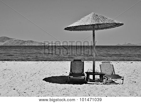 Greece. Kos Island. Two Chairs And Umbrella On The Beach. In Black And White