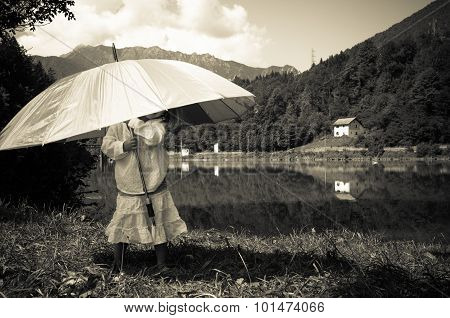 Child Plays With An Umbrella Near The Lake With Black And Withe Style