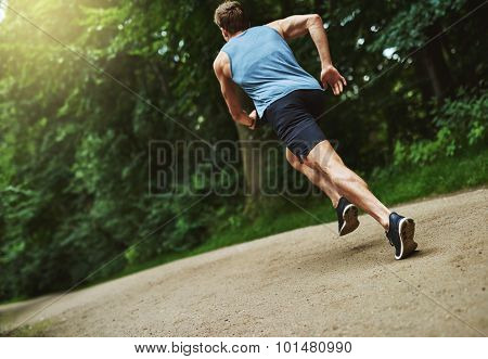 Rear View Of An Athletic Man Jogging At The Park