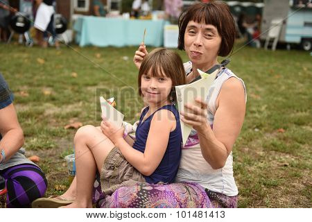 Mom & daughter eat on the grass