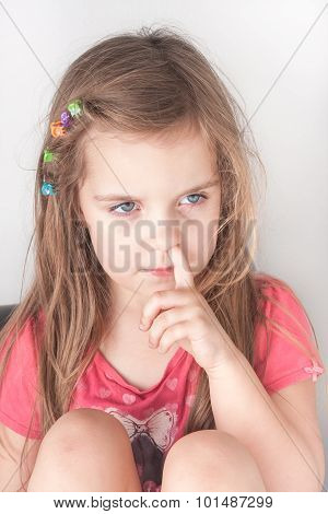 a portrait of a little girl picking her nose