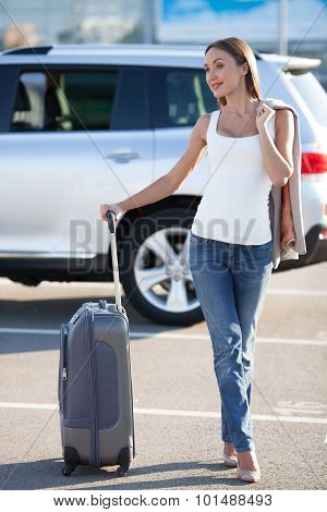 Beautiful young girl with luggage near her transport