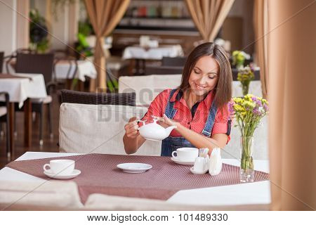 Beautiful hipster girl is enjoying hot drink in cafe
