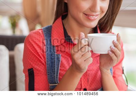 Cheerful young hipster girl is resting in cafe