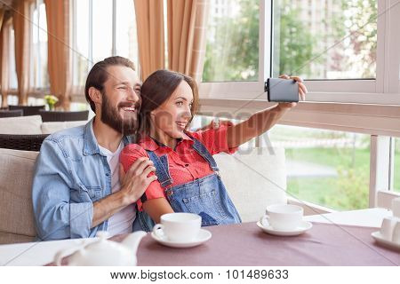 Cheerful young man and woman are making selfie in cafeteria