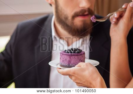 Cheerful loving couple is eating sweet food in restaurant