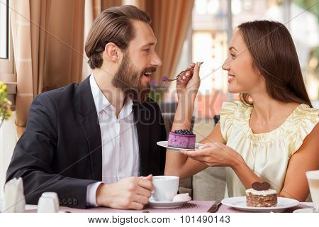 Attractive young man and woman are resting in cafe