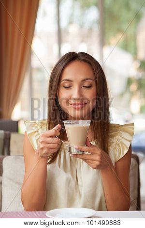 Cheerful young woman is resting in cafe