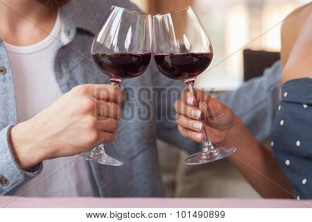 Pretty man and woman are drinking alcohol in cafe