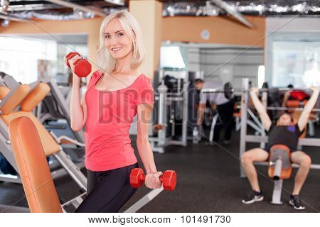 Attractive young female athlete is training in gym
