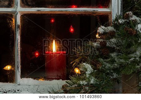 Glowing Christmas Candle In Frosted Home Window