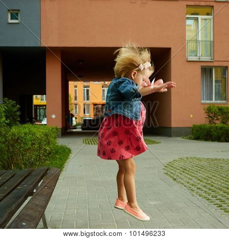 Happy little child, blonde toddler girl jumping