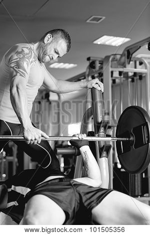 Personal Trainer Helping A Man With Barbell.
