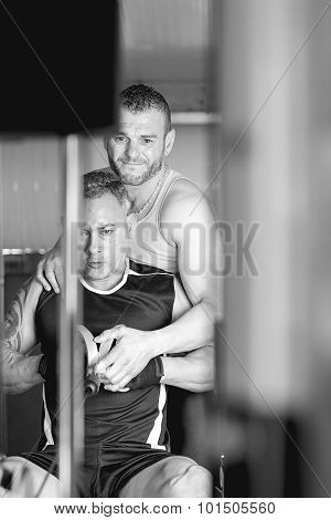 Personal Trainer Helping Man At The Gym.