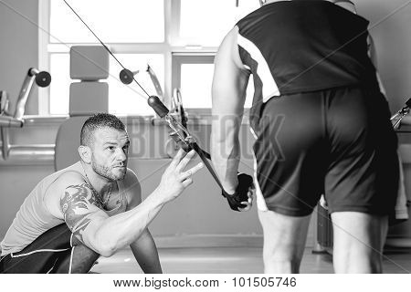 Personal Trainer Helping Man With Dorsal Exercise.