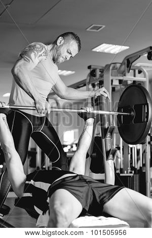 Personal Trainer Instructing A Man With Barbell.