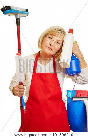 Exhausted cleaning lady with many cleaning supplies in her hands