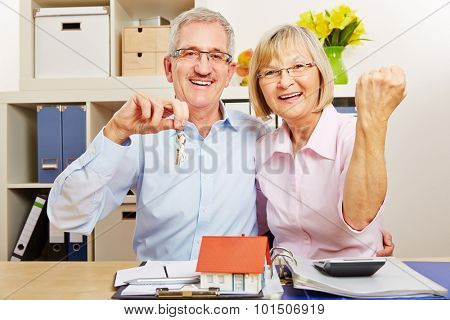 Happy senior couple cheering together with small house and door keys