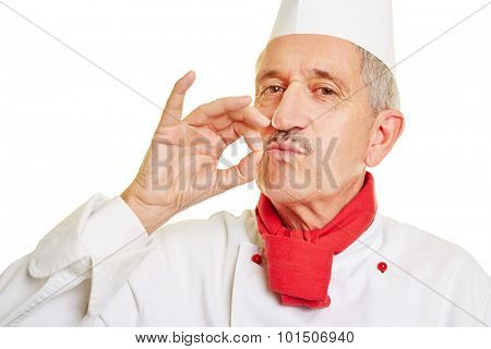 Happy old chef cook making gesture for good taste with his fingers