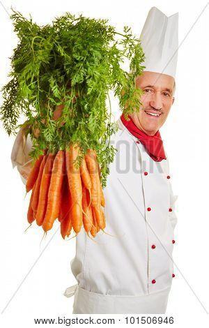 Smiling chef cook showing fresh bunch of carrots