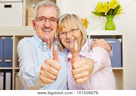 Happy couple of senior citizens holding thumbs up together