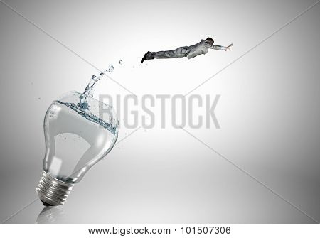 Conceptual image with light bulb filled with clear water and businessman inside