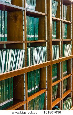 Green books on the bookshelf in university library, full of education knowledge