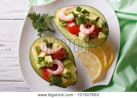Avocado Filled With Shrimp Salad And Vegetables Closeup. Horizontal Top View