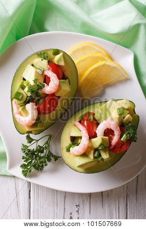 Avocado Filled With Shrimp Salad And Vegetables Closeup. Vertical Top View